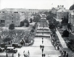 Black and white photo of the Corps of Cadets standing in formation on a campus street.